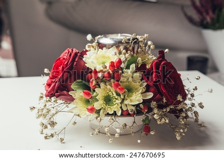 Christmas arrangement of red roses on white table - stock photo