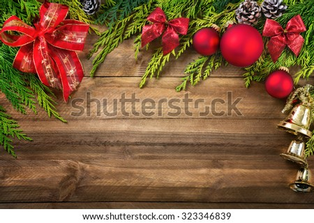 Christmas arrangement with conifer branches, red bows and baubles, pine cones and gold bells bordering a rustic wood planks background - stock photo
