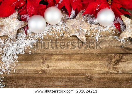 Christmas arrangement with poinsettia, wooden stars, white baubles and snowflakes bordering a rustic wood planks background - stock photo