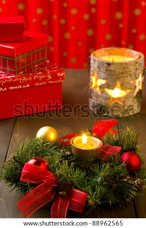 Christmas arrangement with wreath, balls, candles and gift boxes - stock photo