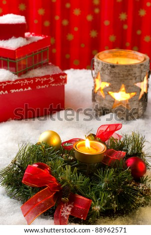 Christmas arrangement with wreath, balls, candles and gift boxes, covered with snow - stock photo