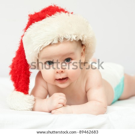 Christmas baby. A blue eyed baby in Santa hat looking at camera - stock photo