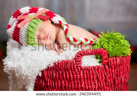 Christmas Baby.  Adorable newborn fast asleep in a red basket and wearing a long read and white striped hat.   - stock photo