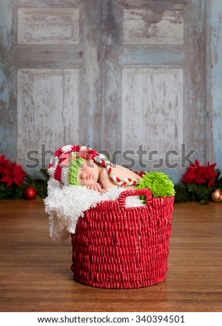 Christmas Baby.  Adorable newborn fast asleep in a red basket and wearing a long read and white striped hat.  Christmas decor in the background.  Room for your text. - stock photo