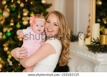 Christmas baby girl with blond hair mother - stock photo