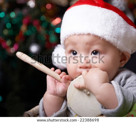christmas baby holding a toy drum. - stock photo