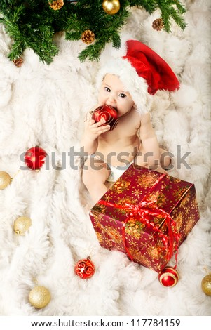 Christmas baby in red hat sitting on fur and eating gift new year ball - stock photo
