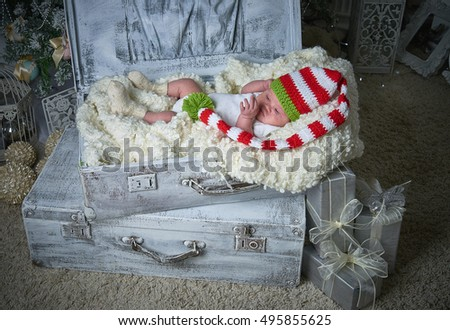 Christmas baby in the suitcase lying under the Christmas tree, Happy New Year, Merry Christmas, gifts, Christmas toys. Studio photo.