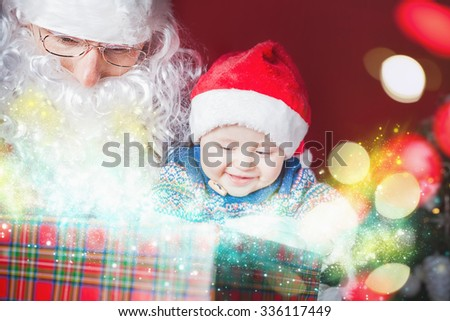 Christmas baby wearing a Santa Claus hat and Santa opening a present and gift box! Night, xmas eve, surprise. Magical light. Design. New Year - stock photo