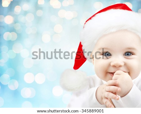 christmas, babyhood, childhood and people concept - happy baby in santa hat over blue holidays lights background - stock photo
