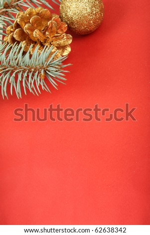 Christmas background, bauble, cone and branch on red - stock photo