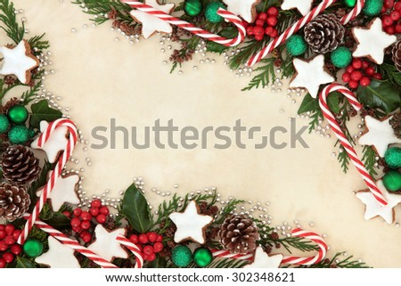 Christmas background border of gingerbread biscuits,  candy canes, bauble decorations, holly and winter greenery over old parchment paper. - stock photo