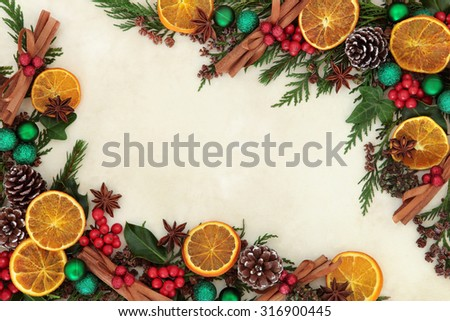 Christmas background border with dried fruit and spices, green bauble decorations, holly and winter greenery over old parchment paper. - stock photo