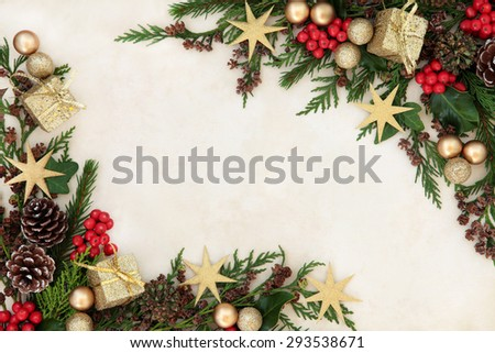 Christmas background border with gold bauble decorations, holly, mistletoe, fir and cedar cypress greenery on old parchment paper. - stock photo