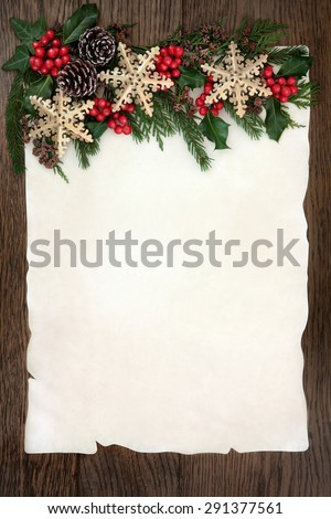 Christmas background border with gold snowflake bauble decorations, holly, ivy, cedar cypress and fir on parchment paper over old oak wood. - stock photo