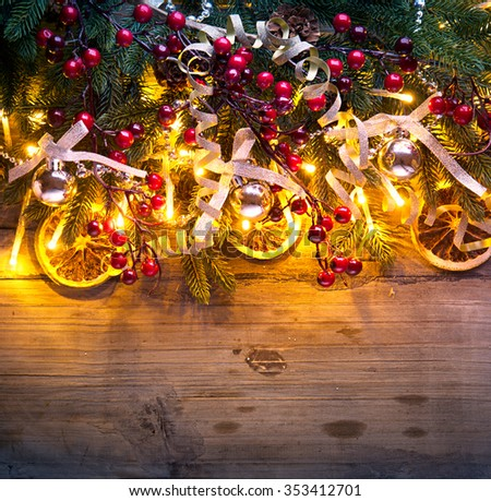 Christmas Background. Christmas fir tree with decoration on dark wooden table. Border art design with Christmas tree, baubles and light garland - stock photo