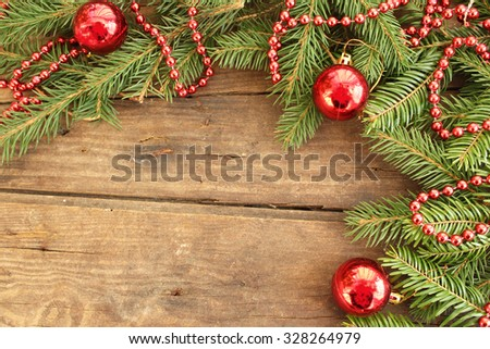 Christmas background - Christmas ornaments in bauble shape on fir tree - on wooden background - stock photo