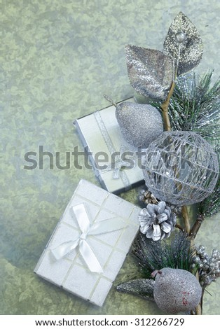 Christmas background fir branches with silver decorations and gift box - stock photo