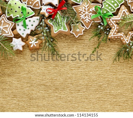 Christmas background. Ginger and Honey cookies with fir tree branches and bows on the gold wrapping paper background. - stock photo