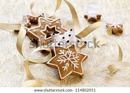 Christmas background. Ginger and Honey cookies with white sugar decoration and gold ribbons. - stock photo