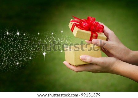christmas background hand holding with gift magic star and text space