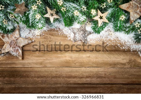 Christmas background in natural wood style, rustic, simple and elegant, with a border of fir branches, wooden stars and snow - stock photo