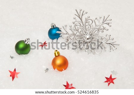 Christmas background. Multicolored Christmas ornaments, snowflake in snow
