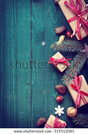 Christmas background of festive gifts, nuts, pine branches and snowflake decorations with copyspace for a seasonal greeting on rustic green wooden boards with side vignette - stock photo