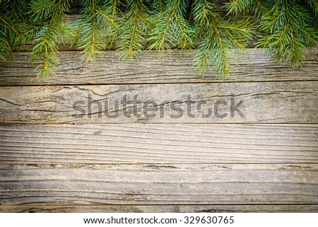 Christmas background of fir tree branches on an old vintage wooden board, copy space for text, top view.