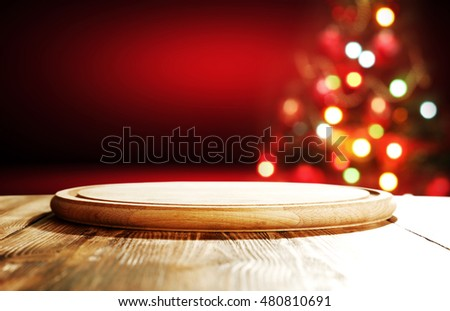 christmas background of wooden desk and red wall with xmas tree