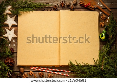 Christmas background - old blank open book with decorations around on vintage planked wood table from above. Layout with free text space. - stock photo