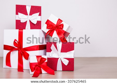 Christmas background - red and white present boxes on wooden floor with copy space - stock photo