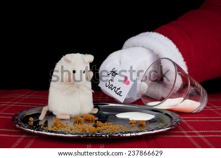 Christmas background. Santa Claus shows a greeting card to a mouse, that has eaten Santa's cookies and drunk milk. - stock photo