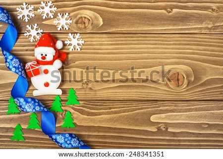 Christmas background - snowman, snowflakes and blue ribbon on wooden table - stock photo
