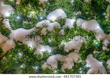 Christmas background. Spruce with snow and garland lights