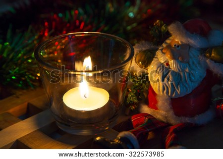 Christmas background tea candles and toy Santa - stock photo