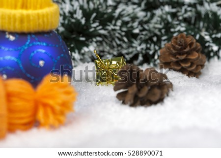 Christmas background with a blue ornament, golden gift box, Angels, berries and fir in snow on forest backround