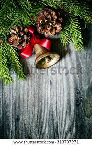 Christmas background with a bronze bell, pine cones and spruce paws, selective focus - stock photo