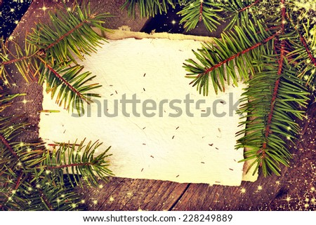 Christmas background with a Christmas decoration, fir branches with blank paper on wooden planks, wooden table background, New year theme - stock photo
