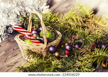 Christmas background with a red and white candies, decoration in a little wicker basket, fir branches on wooden planks, wooden table background, New year theme - stock photo
