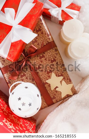 Christmas background with a red ornament, golden gift box, berries and fir in snow