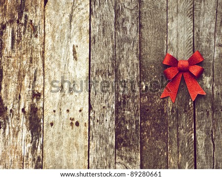 Christmas background with a sparkling red Christmas bow on a grunge wooden backdrop with copy space. - stock photo