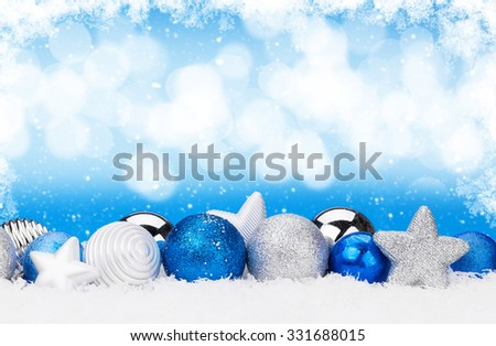 Christmas background with baubles in snow and bokeh copy space - stock photo