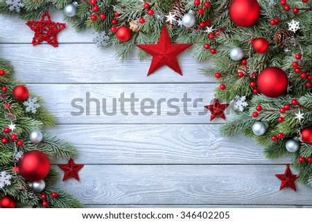 Christmas background with blue wooden board and fir branches decorated with red and silver baubles and stars - modern, simple and elegant - stock photo