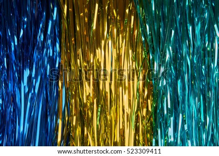 Christmas background with blue, yellow and green tinsel
