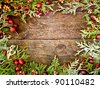Christmas background with cedar sprigs, berries, and maple keys on a grunge wood backdrop with copy space. - stock photo