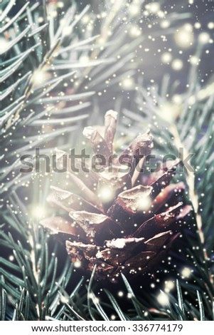 Christmas background with christmas decoration. Festive pine cone with falling snow flakes. Card or invitation.