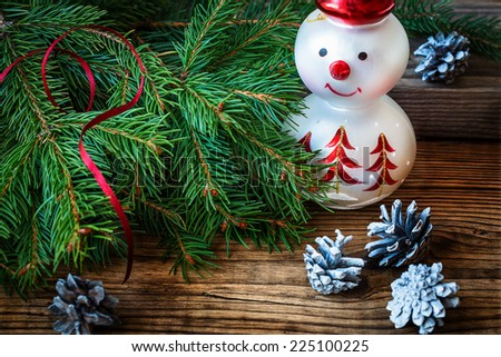 Christmas background with Christmas tree and snowman on a rustic wooden board - stock photo