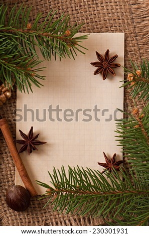 Christmas background with cinnamon, star anise, nutmeg and old paper on the background of old cloth fabric - stock photo