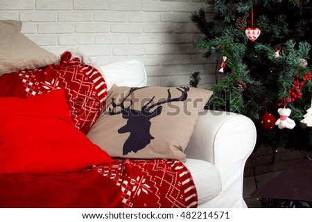 Christmas background with classic New Year Tree decoration, red sofa and pillow with deer print